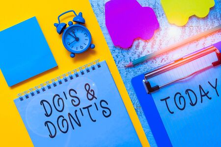 Writing note showing Do S And Don T S. Business concept for Confusion in one s is mind about something Notepad clipboard sheet marker car sticks alarm clock wooden background Stock Photo