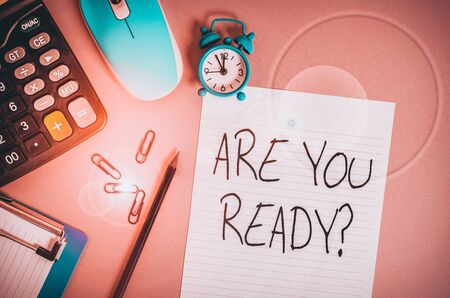 Handwriting text Are You Ready Question. Conceptual photo used telling someone start something when feel prepared Calculator clips clock clipboard mouse sheet pencil colored background Stock Photo