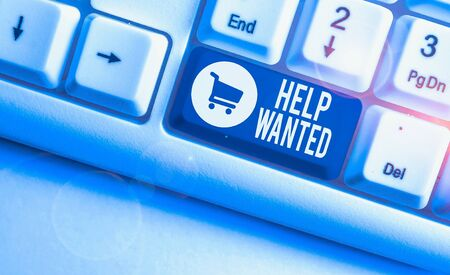 Writing note showing Help Wanted. Business concept for An ad in the paper an employer places to find a new employee White pc keyboard with note paper above the white background