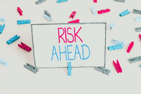 Word writing text Risk Ahead. Business photo showcasing A probability or threat of damage, injury, liability, loss Colored clothespin papers empty reminder yellow floor background office