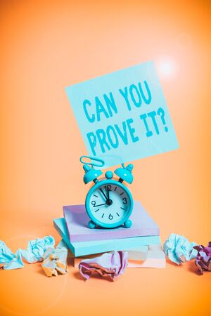 Text sign showing Can You Prove It Question. Business photo showcasing Asking Someone for evidence or approval Court Alarm clock sticky note paper balls stacked notepads colored background 版權商用圖片