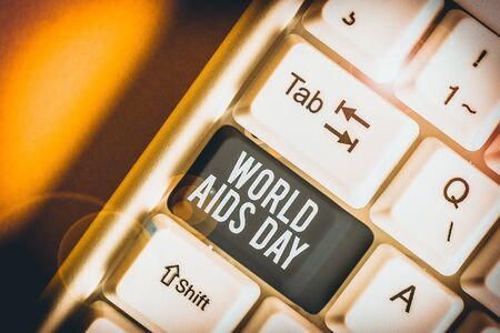 Conceptual hand writing showing World Aids Day. Concept meaning 1st December dedicated to raising awareness of the AIDS White pc keyboard with note paper above the white background