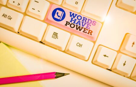 Conceptual hand writing showing Words Have Power. Concept meaning Energy Ability to heal help hinder humble and humiliate White pc keyboard with note paper above the white background