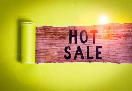 Word writing text Hot Sale. Business photo showcasing putting products on high discount Great price Black Friday Cardboard which is torn in the middle placed above a wooden classic table