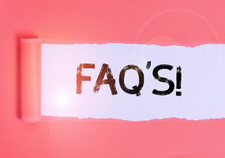 Text sign showing Faq's. Business photo text a list of questions and answers relating to a particular subject Cardboard which is torn in the middle placed above a plain table backdrop