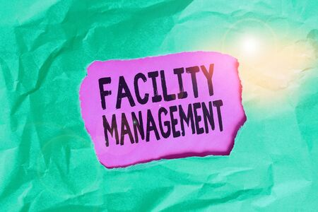 Word writing text Facility Management. Business photo showcasing maintenance of an organization s is buildings and equipment Green crumpled ripped colored paper sheet centre torn colorful background