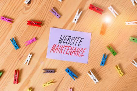 Text sign showing Website Maintenance. Business photo showcasing act of regularly checking your website for issues Colored clothespin papers empty reminder wooden floor background office