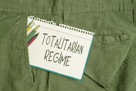 Word writing text Totalitarian Regime. Business photo showcasing mode of government that prohibits opposition parties Writing equipment and white note paper inside pocket of man work trousers