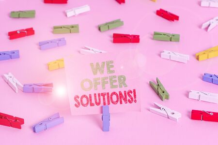 Text sign showing We Offer Solutions. Business photo showcasing Offering help assistance Experts advice strategies ideas Colored clothespin papers empty reminder pink floor background office pin 写真素材
