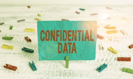 Word writing text Confidential Data. Business photo showcasing information that is not available to the general public Green clothespin white wood background colored paper reminder office supply