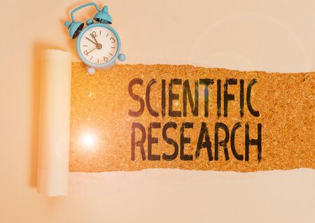Writing note showing Scientific Research. Business concept for methodical study to prove or disprove a hypothesis Alarm clock and torn cardboard on a wooden classic table backdrop