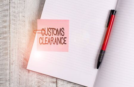 Word writing text Customs Clearance. Business photo showcasing documentations required to facilitate export or imports Thick pages notebook stationary placed above classic look wooden backdrop Stock Photo