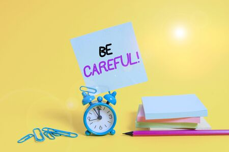 Conceptual hand writing showing Be Careful. Concept meaning making sure of avoiding potential danger mishap or harm Alarm clock pencil clips note stacked notepads colored background