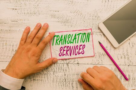 Conceptual hand writing showing Translation Services. Concept meaning organization that provide showing to translate speech Hand hold note paper near writing equipment and smartphone