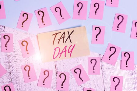 Conceptual hand writing showing Tax Day. Concept meaning colloquial term for time on which individual income tax returns Crumbling papers with thick cardboard on the wooden table
