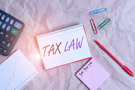 Conceptual hand writing showing Tax Law. Concept meaning governmental assessment upon property value or transactions Papercraft desk square spiral notebook office study supplies Reklamní fotografie