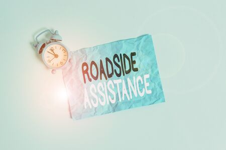 Conceptual hand writing showing Roadside Assistance. Concept meaning helps drivers when their vehicle breaks down on the road Metal vintage alarm clock crush sheet sky colored background