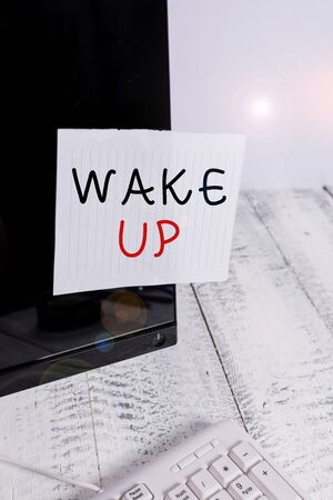 Text sign showing Wake Up. Business photo text an instance of a demonstrating waking up or being woken up Rise up Notation paper taped to black computer monitor screen near white keyboard