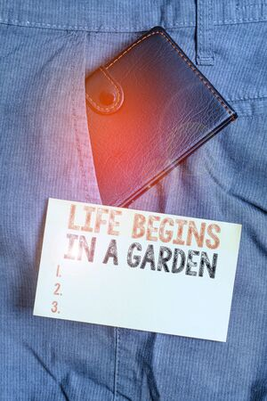 Writing note showing Life Begins In A Garden. Business concept for Agriculture Plants growing loving for gardening Small wallet inside trouser front pocket near notation paper