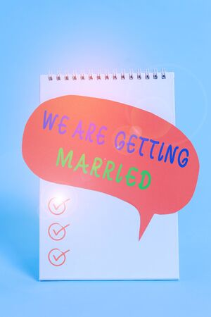 Word writing text We Are Getting Married. Business photo showcasing Engagement Wedding preparation Loving couple Standing blank spiral notepad speech bubble lying cool pastel background Foto de archivo