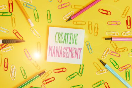 Handwriting text writing Creative Management. Conceptual photo Managing of creative thinking skills and mental process Flat lay above empty paper with copy space pencils and colored paper clips