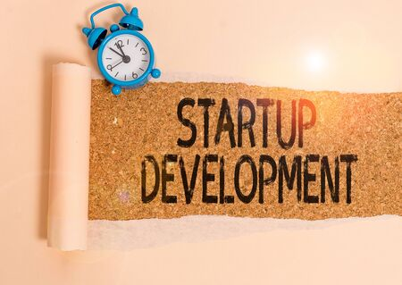Writing note showing Startup Development. Business concept for efficiently develop and validate scalable business model Alarm clock and torn cardboard on a wooden classic table backdrop