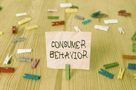 消費者行動を示す概念的な手書き。個々の顧客がブランドとどのように相互作用するかについての概念的な意味研究 着色されたくしゃくしゃの紙木製の床の背景の衣服ピン