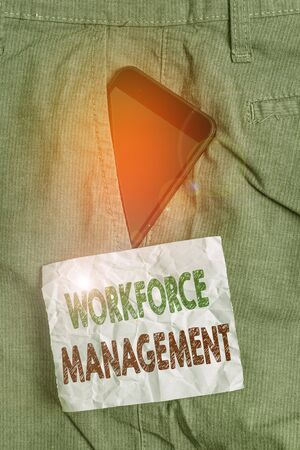 Handwriting text Workforce Management. Conceptual photo use to optimize the productivity of its employees Smartphone device inside formal work trousers front pocket near note paper Stock Photo