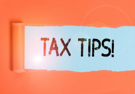 Text sign showing Tax Tips. Business photo text compulsory contribution to state revenue levied by government Cardboard which is torn in the middle placed above a plain table backdrop