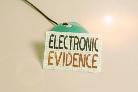 Writing note showing Electronic Evidence. Business concept for probative information stored or transmit in digital form Wire vintage electronic mouse squared paper sheet colored background Reklamní fotografie