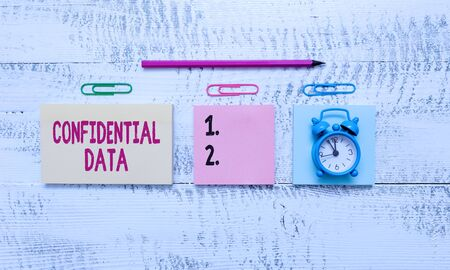 Conceptual hand writing showing Confidential Data. Concept meaning information that is not available to the general public Blank notepads marker small alarm clock wooden vintage background Reklamní fotografie