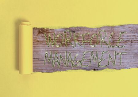Conceptual hand writing showing Workforce Management. Concept meaning use to optimize the productivity of its employees Cardboard which is torn placed above a wooden classic table