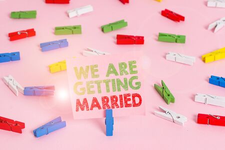 Text sign showing We Are Getting Married. Business photo showcasing Engagement Wedding preparation Loving couple Colored clothespin papers empty reminder pink floor background office pin