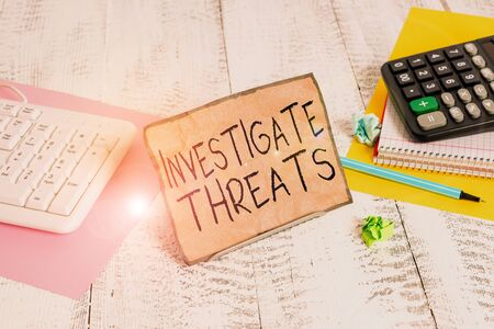 Text sign showing Investigate Threats. Business photo showcasing carry out a systematic inquiry on potential danger Notepaper stand on buffer wire in between computer keyboard and math sheets