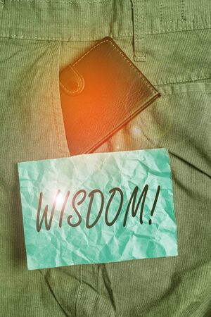 Text sign showing Wisdom. Business photo showcasing the ability to use your knowledge and experience to make decisions Small little wallet inside man trousers front pocket near notation paper Stockfoto