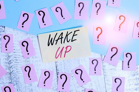 Conceptual hand writing showing Wake Up. Concept meaning an instance of a demonstrating waking up or being woken up Rise up Crumbling papers with thick cardboard on the wooden table