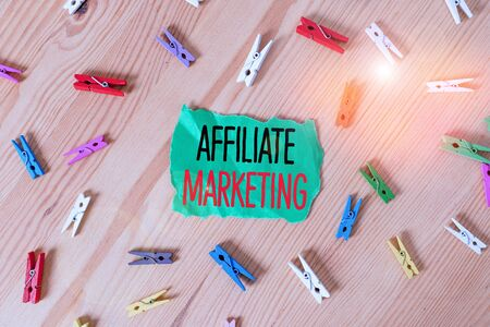 Conceptual hand writing showing Affiliate Marketing. Concept meaning compensation to thirdparty publishers to generate leads Colored crumpled papers wooden floor background clothespin