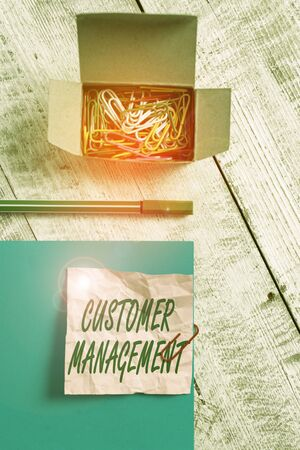 Conceptual hand writing showing Customer Management. Concept meaning customer retention and ultimately driving sales growth Wrinkle paper and cardboard placed above wooden background Stock Photo