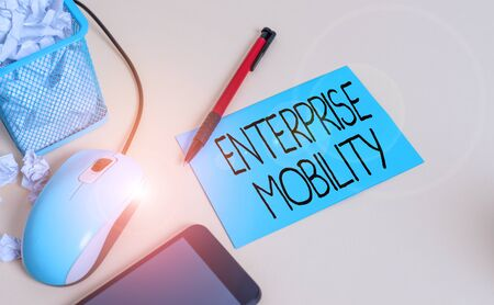 Conceptual hand writing showing Enterprise Mobility. Concept meaning Employees do jobs remotely using a mobile devices crumpled paper in bin placed next to modern gadget and stationary 版權商用圖片