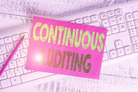 Handwriting text writing Continuous Auditing. Conceptual photo Internal process that examines accounting practices White keyboard office supplies empty rectangle shaped paper reminder wood