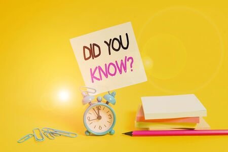 Conceptual hand writing showing Did You Know Question. Concept meaning when you are asking someone if they know fact or event Alarm clock pencil clips note stacked notepads colored background Фото со стока