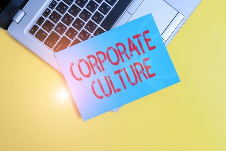 Text sign showing Corporate Culture. Business photo showcasing beliefs and attitudes that characterize a company Part view trendy metallic laptop clipboard paper sheet colored background 스톡 콘텐츠
