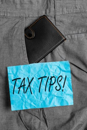 Text sign showing Tax Tips. Business photo showcasing compulsory contribution to state revenue levied by government Small little wallet inside man trousers front pocket near notation paper