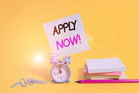 Conceptual hand writing showing Apply Now. Concept meaning request something officially in writing or by sending in form Alarm clock pencil clips note stacked notepads colored background Stock Photo