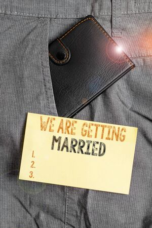 Writing note showing We Are Getting Married. Business concept for Engagement Wedding preparation Loving couple Small wallet inside trouser front pocket near notation paper Foto de archivo