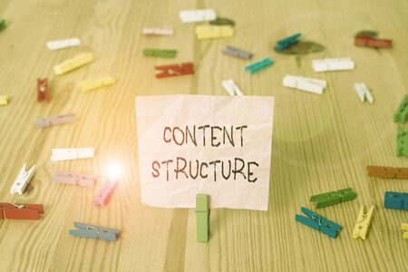 Conceptual hand writing showing Content Structure. Concept meaning information that is organized in a predictable way Colored crumpled papers wooden floor background clothespin