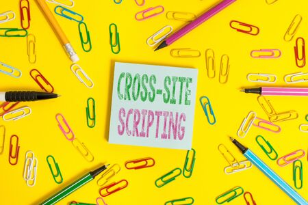 Handwriting text writing Cross Site Scripting. Conceptual photo Security vulnerability mainly found in web application Flat lay above empty paper with copy space pencils and colored paper clips