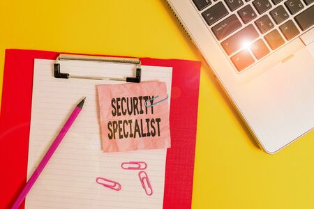 Writing note showing Security Specialist. Business concept for specializes in the security of showing assets or systems Laptop clipboard paper sheet clips pencil crushed colored background Stok Fotoğraf
