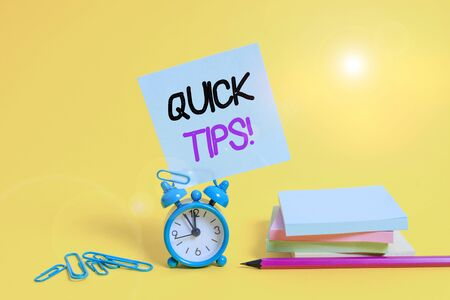 Conceptual hand writing showing Quick Tips. Concept meaning small but particularly useful piece of practical advice Alarm clock pencil clips note stacked notepads colored background