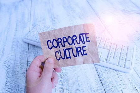 Writing note showing Corporate Culture. Business concept for beliefs and attitudes that characterize a company Man holding colorful reminder square shaped paper wood floor